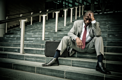 Frustrated guy, head in hands on steps in suit